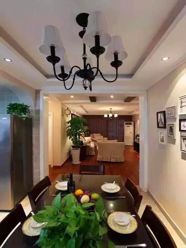 餐厅的餐桌选择实木为主,深红色的实木餐桌搭配纹样丰富的餐具相得益彰,餐厅墙面的照片墙将来会是整个家旅游归来的分享区。设计格局上面把餐厅和厨房是连在一个空间,只有中间的吧台隔断,使得空间更加开阔。