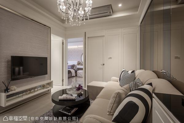 设计师郑高玮与林妤如运用石材纹的壁纸作为电视主墙的立面表现,并以烤漆与镜框来围塑优美的新古典元素。