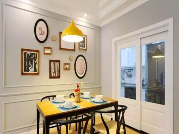 黑色铁艺餐桌配上木色桌面,一盏宜家吊灯,照片墙做装饰。