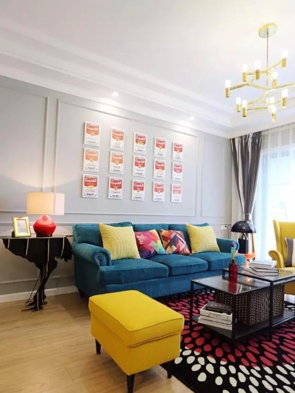 蓝色的大沙发,黄色的老虎椅和单人位沙发凳,造型别致的黑色铁艺家具。墙上的一组系列装饰明显的波普风特色。