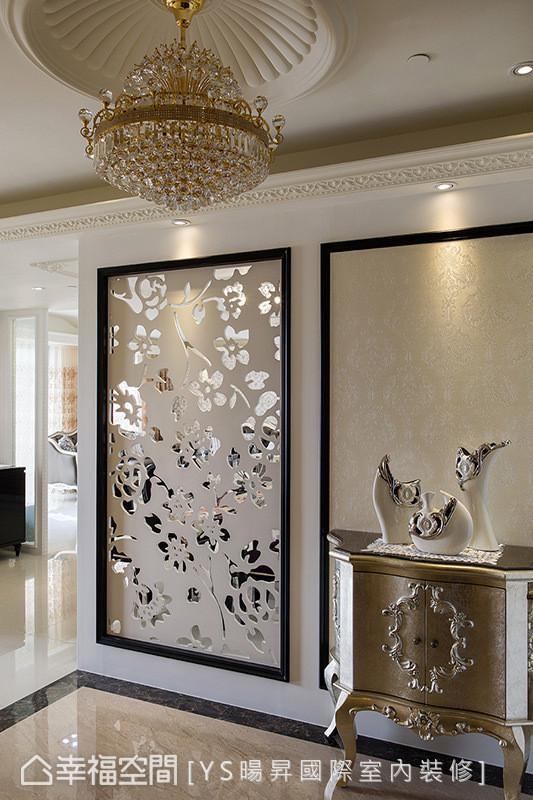 玄关天花以垂吊式水晶灯,雕花镂空感的屏风,金色系古典矮柜以及艺术