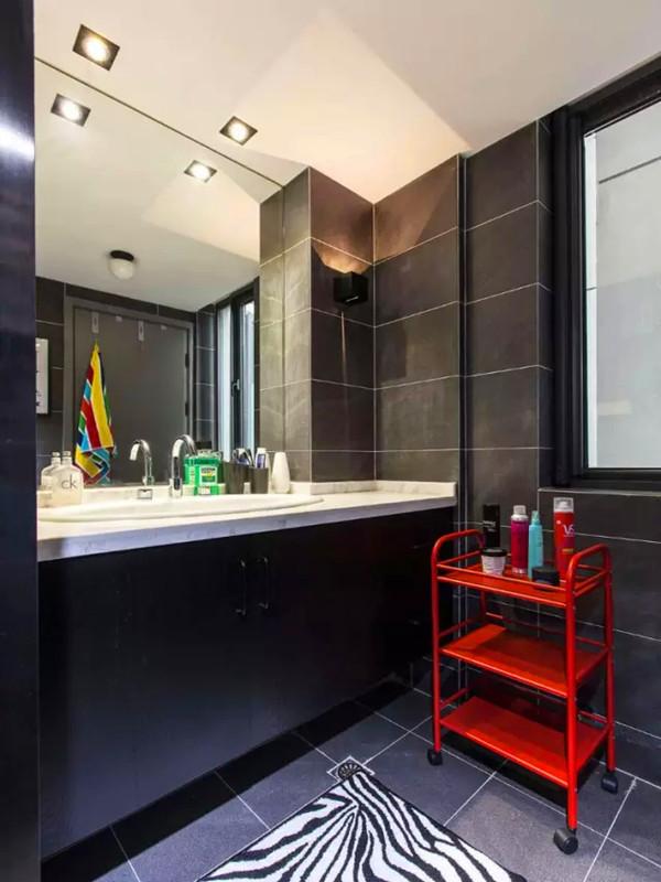 黑色调的卫生间用红色置物架点缀。