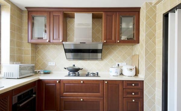 厨房选用咖啡色整体橱柜,配以金属质感的现代化电器,大气又方便实用