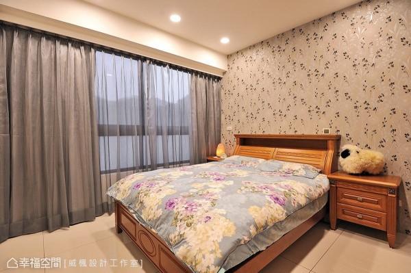 床头壁面以黑白色系的花草图案壁纸做铺陈,烘托出床头柜的木色质感。