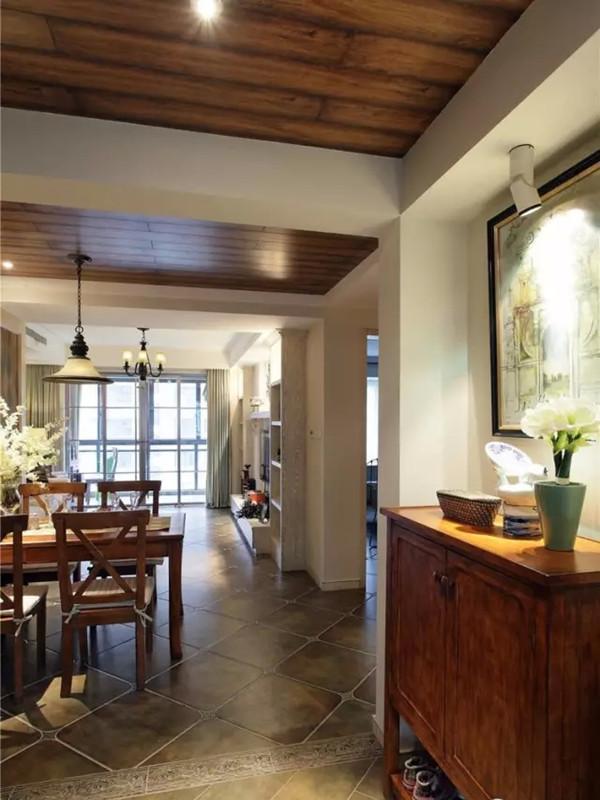 左手边是餐厅和客厅,地面是泛着青色的仿古砖。