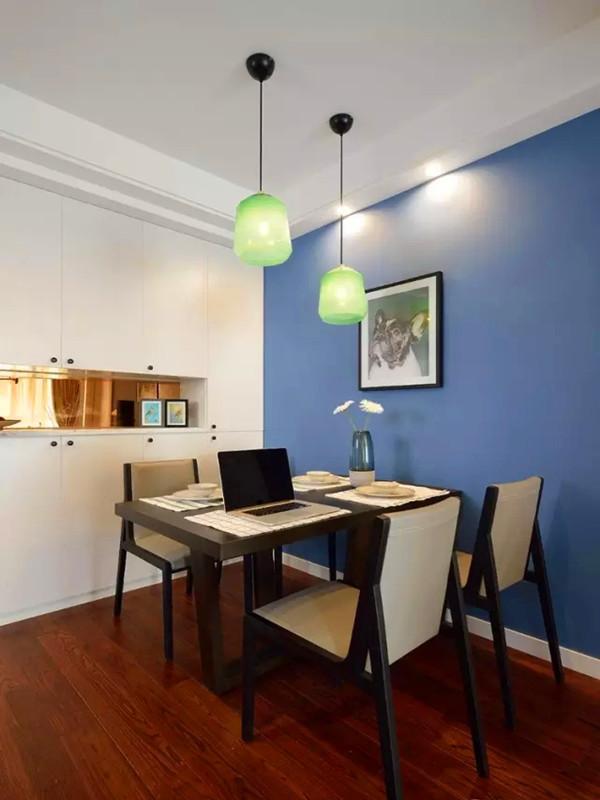 经过玄关便进入餐厅,黑色餐桌椅和白色餐边柜的对比强烈,蓝色背景墙和绿色吊灯也是混搭的彻底。