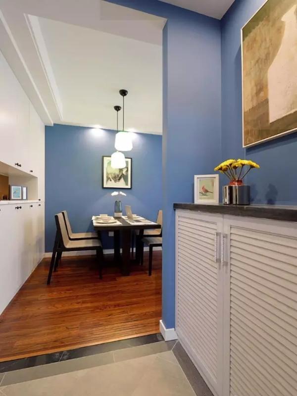 进门玄关用复古砖和室内地板区分,百叶鞋柜简洁实用,蓝色的墙面用装饰画点缀。