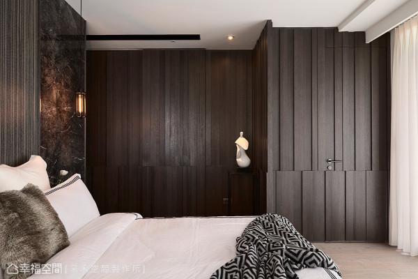 沉稳静谧的木皮墙面,隐藏主卧卫浴与更衣室的入口门片,其立体线条的处理方式,在光线映照下更突显丰富的肌理。