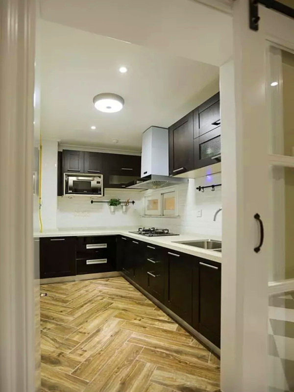 厨房间地面用木纹砖人字形铺贴,黑色橱柜,白色墙面,黑白分明,墙上的小窗户开往餐厅,增加空间之间的互动,也可以传菜。