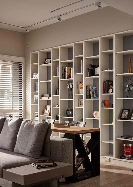 沙发后方摆设一张简约感的书桌,并利用展示柜体,营造出轻快且独特的生活节奏。