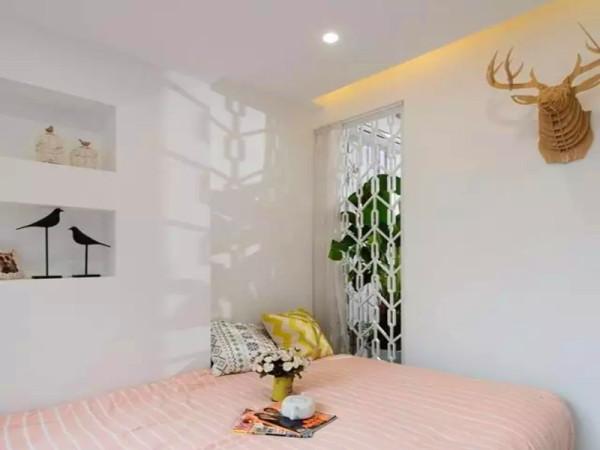 次卧和客厅之间的墙面两侧是雕花隔断设置,保证了采光和通透性,为了隐私,客厅都放置了大盆的绿植,次卧这边有安装帘子。