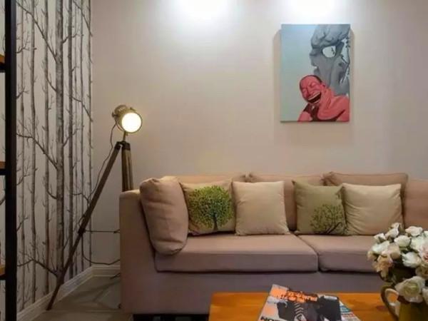 灰色布艺沙发,背景墙上是岳敏君「傻笑人」系列的复制装饰画。