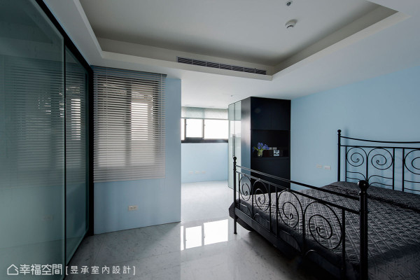长辈房以天蓝色调舒缓氛围,而曲线造型的黑铁床架则延续工业风韵味,至于床尾墙柜选用玻璃门片可减缓墙阻感。