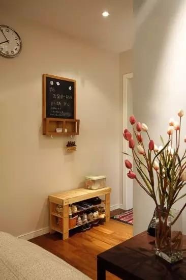 玄关只有1㎡,大的玄关柜显然不合适,在墙面挂个小装饰, 挡住丑陋的电箱,下面放置换鞋凳,清爽也实用。