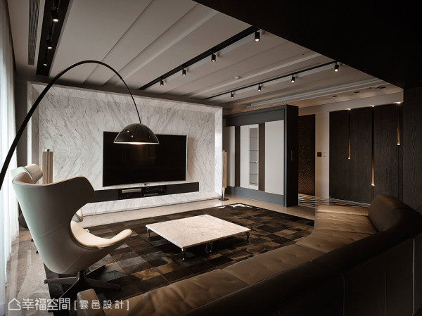 云邑设计以纯熟而精准的手法铺述客厅面貌,例如电视主墙采用银狐大理石,并以45度导角的造型来框塑,天花板则以线条、沟缝与灯轨作为纵向的延伸,无形中放大了视觉的尺度。