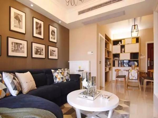 从客厅望向餐厅,白色的茶几和几何图案的抱枕点缀了深色调的空间。
