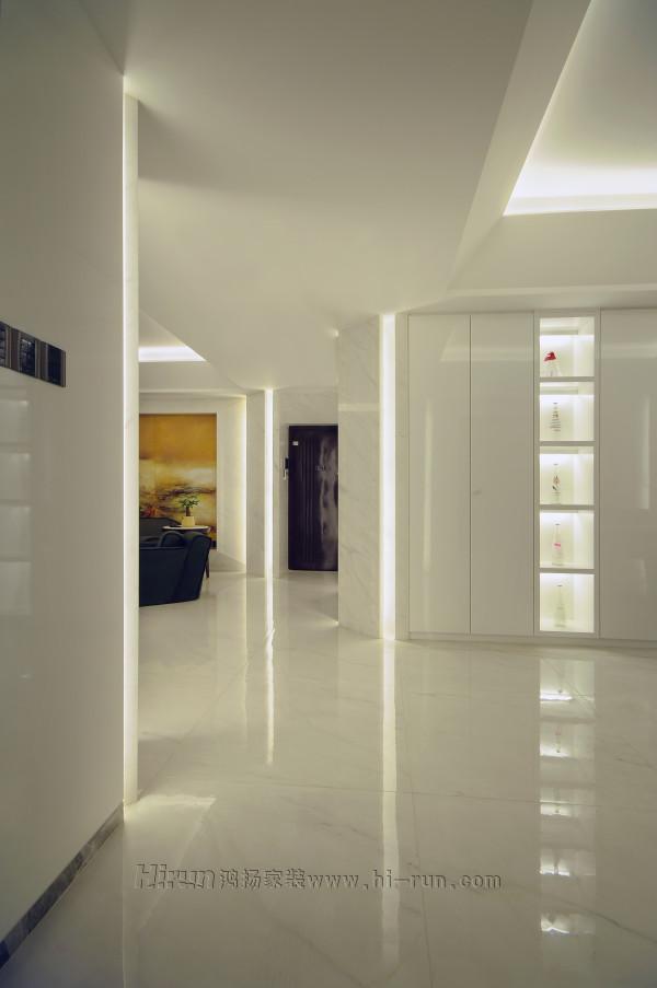 入户亮光白的鞋柜与雅士白大理石收边,及与转角处的餐厅酒柜,墙板,隐形门木制构件形成一个整体。