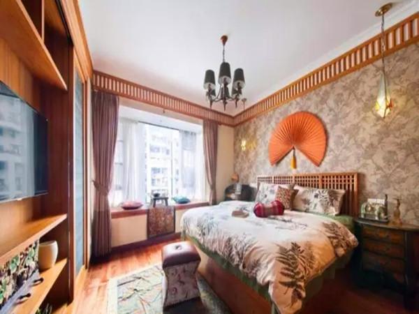 主卧从床头墙纸到床品都采用热带花卉树图案,一把橙色的热带挂扇。