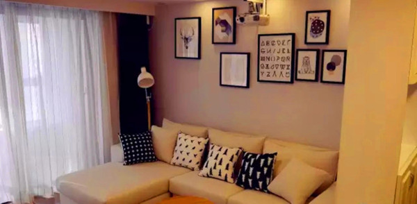 木质地板营造出一种温和的自然感,北欧风的极简地灯与白色沙发干净利落,特别适合小空间的摆放。而错落有致的照片墙又中和些许的冷淡,雪白的纱质窗帘在微风的吹动下,如梦似幻。