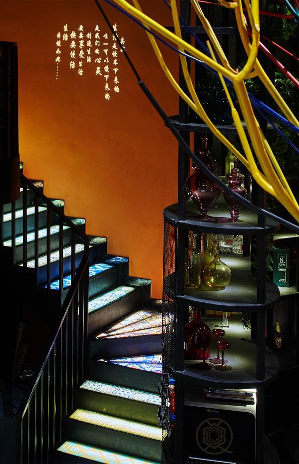 通往二楼的楼梯就藏在吧台酒水架的后面。楼梯很特别,是定制的彩绘玻璃,灵感来自蜀绣与川剧变脸中浓墨重彩之印象。玻璃下有暗藏的LED灯管,昼夜都闪耀着光芒。而生活中斑斓的那一面,此刻就集中在这里。