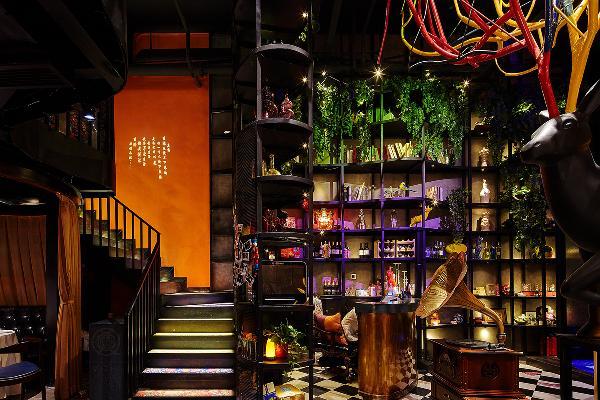 酒水架上散落小小的LED灯珠,顶部有五色光源的水波纹灯照过来,明灭起伏。酒水架前的定制吧台,运用两种撞色,蓝绿与旧金山的艺术漆面。