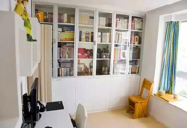 另一面墙是书柜,上半部是带玻璃门的书柜,下半部分是封闭的收纳柜,可以放一些杂物