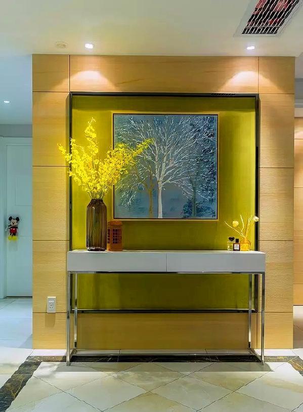 ▲ 建筑面积139平,进门玄关区端景是一面黄绿色的墙,以科定饰面板做底,装饰画点缀,配合不锈钢脚的白色条案