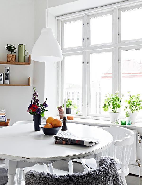 白色饭桌,窗台一些绿色植物的装饰