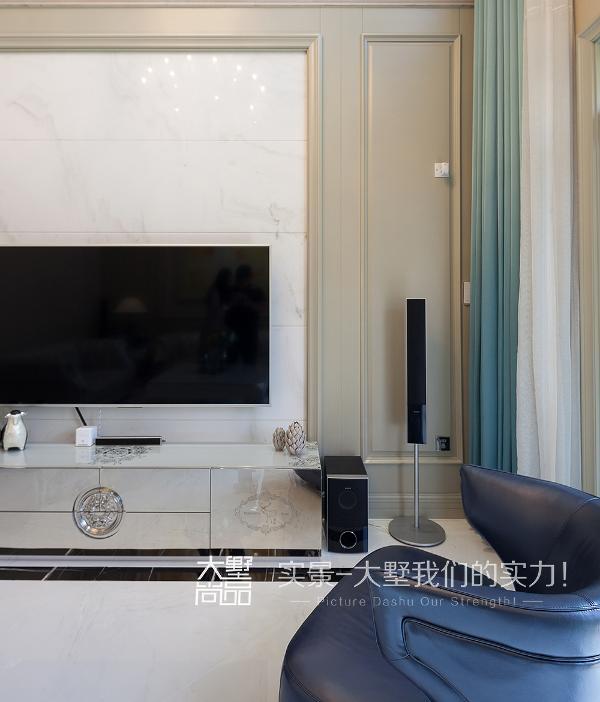 整个电视背景也是与沙发背景相统一,采用了定制护墙与这样一款白色大纹理石材来呼应整个空间,在后期巨型水晶吊灯及蓝色落地窗帘的衬托下,整个空间大气而又精致。