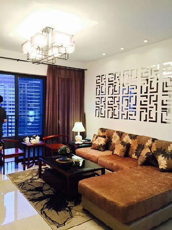 """沙发背景墙打造了一面""""花格镜墙"""",整个""""镜墙""""的构图既像传统的中式龙纹图腾,又像苏州园林的漏窗,花窗式的巧妙设计将原先平面的白墙打穿,墙面显得通透深邃,提升了整个空间的品味。"""