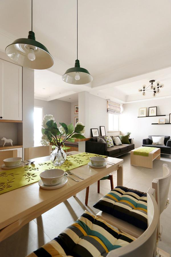 客厅空间简洁大气,室内空间面积比较大,黑色的布艺沙发既耐脏又实用,木质的茶几比较特别,上面摆放绿色额茶几布,带来一丝清新感。墙面空间设计了黑色的置物架用来摆放装饰画。