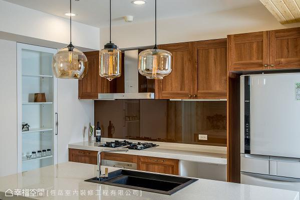 不若一般厨房的冰冷意象,设计师蔡岳儒在柜面处以木纹质感的色调呈现。