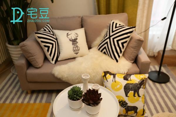 浅灰色的简约沙发与地毯颜色匹配,沙发前的小茶几诠释了简约中的精致,极简轻奢,格调十足。地毯选用了拼色条纹图案,在给房间增添暖感的同时,棉麻质感消解了颜色的张扬使其低调中又不失色韵。