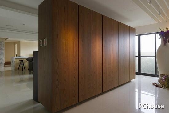 鞋柜兼电视主墙面的双向设计,柚木纹理以量体气势铺排,端景处搭以花器造型,形塑玄关区域。