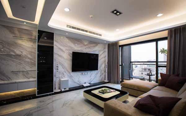 黑玻门扇的电视机柜,兼顾遥控器感应的便利与美观,同时使电视主墙展现完整而大器的石材拼花纹理。