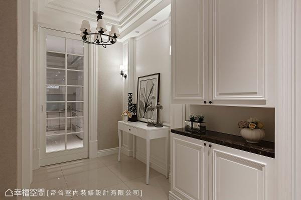 室内电梯前的区域,为进入餐厨区的过道,运用带有美式语汇的灯饰、端景桌与柜体,营造心情转换的地方。