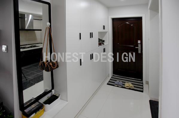 玄关在颜色上采用大面积的白色,局部黑色的运用让空间的层次表达更立体。鞋柜的设计上考虑了穿衣镜的位置,方便主人出行之前整理行装。