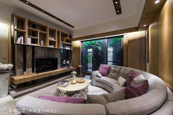 采灰色洞石大理石制作的电视墙,与沙发背墙的温润木皮相对应,结合室外的庭园造景,围塑出休闲舒压的氛围。