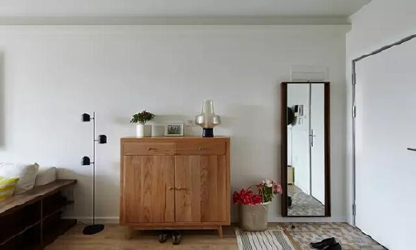 玄关设计非常简单,利用1㎡的地面,铺上俏皮的马赛克地砖,耐脏有格调  。穿衣镜和鞋柜相结合,乱七八糟的鞋子也能整齐的收纳起来。