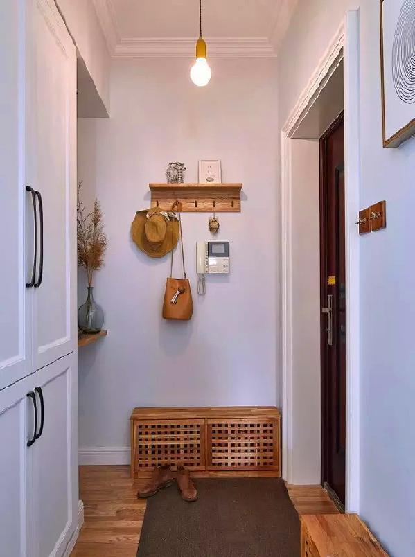 进门玄关处,挂钩、换鞋凳、搁板和地板统一木色,通顶鞋柜设计