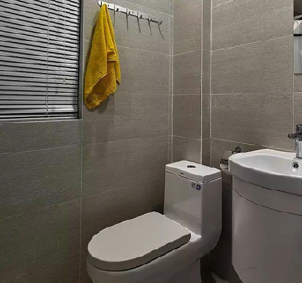 ▲ 卫生间采用灰色纹理墙砖,配合暖色灯光,简单温馨