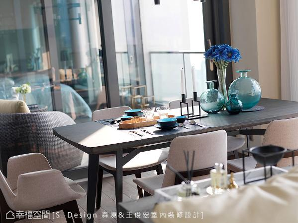 深色木质餐桌上摆设蓝色系杯皿与花器,以身后的海天一色为背景,托衬出一幅美好的夏日飨宴。