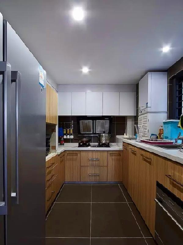 ▲ 木纹橱柜和白色橱柜搭配,高低不同的台面设计考虑了橱柜的易用性,墙面地面采用灰色的瓷砖