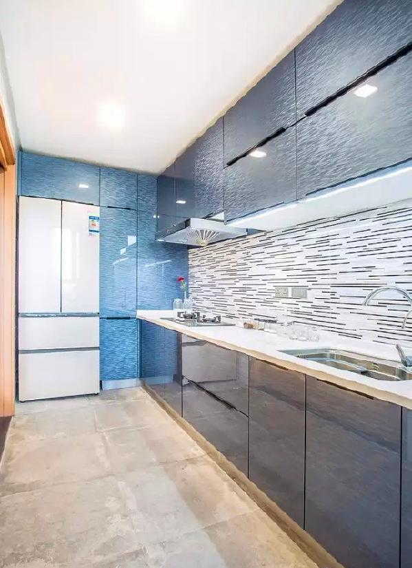 ▲ 厨房用蓝色的烤漆门板和白色台面,冰箱位置嵌入式设计