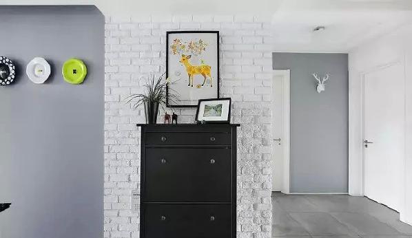 入户玄关处,白色仿古文化砖搭配黑色简约玄关柜,配饰挂画让氛围