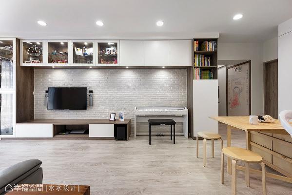 电视主墙铺述温暖调性的文化石,推演悠闲舒适的居家意象,上方并设置一排吊柜,以玻璃及柜面的方式,呈现收纳及展示的多功能。