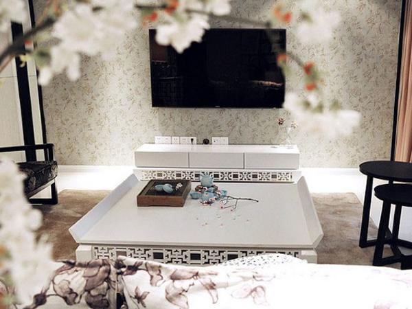 客厅摆放着黑白分明的简约家具,镂空的雕饰极具传统特色。偌大的电视墙不再放置闲杂物件,仅仅一片碎花装饰,凸显出简约式的田园清新风格。陶瓷茶具和梅花树枝很符合古代文人赏花品茶的意境。