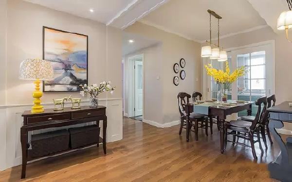 玄关的深色木质柜子,墙上挂一幅画装饰,装饰方面也是采纳的设计师的建议。餐厅也是非常简单的四人长桌,和厨房用玻璃门隔开。