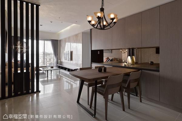 大面开窗的开放空间让自然光静谧地洒下,使整体空间明亮舒适,餐桌旁的大面柜体则作为主要的收纳使用,并以茶镜拉长空间景深。