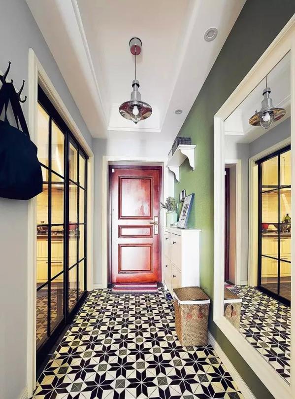 ▲进门玄关区地面采用黑白灰色的花砖铺贴,侧面是厨房的黑色细框玻璃移门